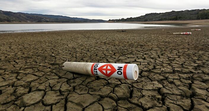 """In this Feb. 4 2014 file photo, a warning buoy sits on the dry, cracked bed of Lake Mendocino near Ukiah, Calif. As bad as the drought in California and the Southwest was last year and in the Midwest a couple years ago, scientists say far worse historic decades-long dry spells are coming. """""""