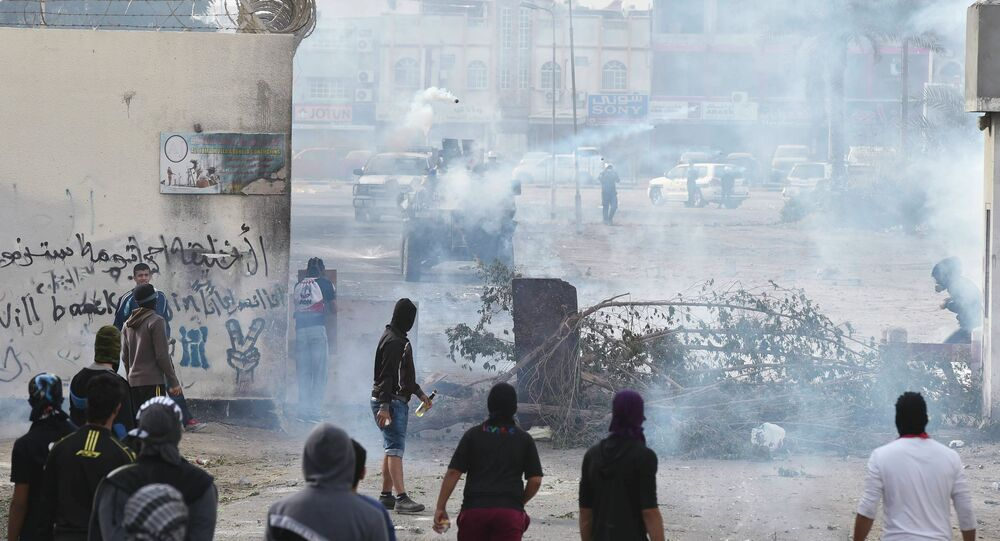 Protesters take cover from tear gas fired by riot police during early morning clashes, on the fourth anniversary of an uprising to demand democratic reforms in Bahrain, in the village of Sanabis, west of Manama.