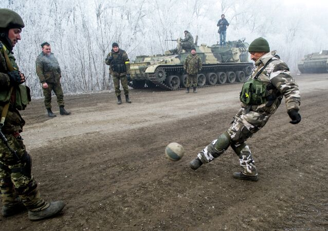 Ukrainian servicemen play football on a road at Svitlodarsk, approaching Debaltseve on February 15, 2015