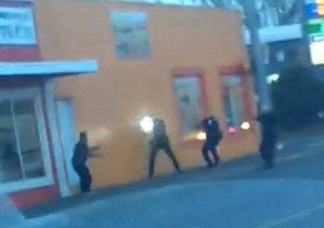In this still frame taken from a cell phone video provided by Dario Infante and taken on Feb. 10, 2015, Antonio Zambrano-Montes, left, turns to face police officers as one holds a flashlight and two others draw their guns just before shooting him in Pasco, Wash.