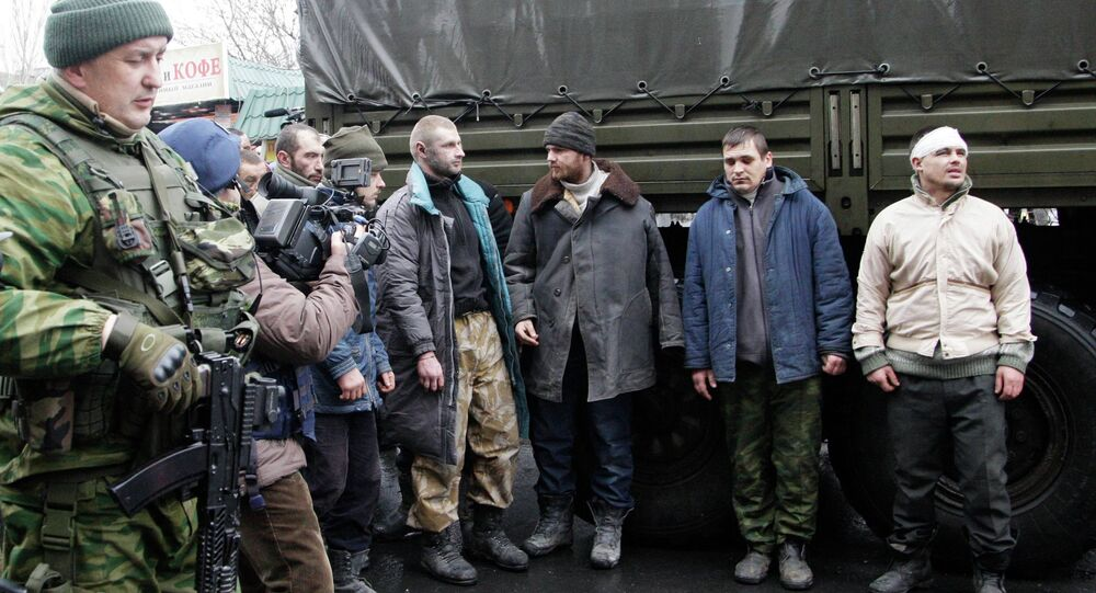 Prisoners of war (POWs), representing Ukrainian armed forces and escorted by members of the armed forces of the separatist self-proclaimed Donetsk People's Republic, line up as they visit a site near the public transport stop, where civilians were earlier killed on Thursday, in Donetsk, January 22, 2015. File photo.