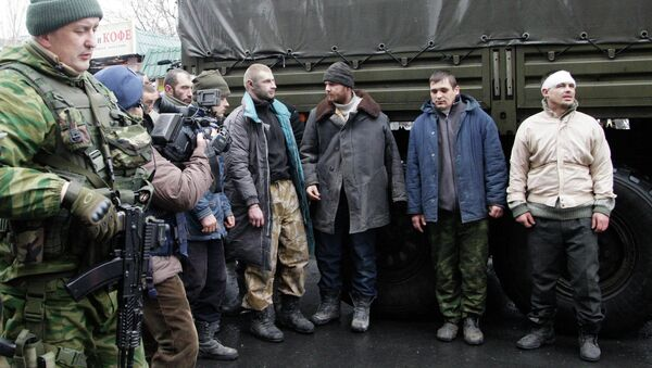 Prisoners of war (POWs), representing Ukrainian armed forces and escorted by members of the armed forces of the separatist self-proclaimed Donetsk People's Republic, line up as they visit a site near the public transport stop, where civilians were earlier killed on Thursday, in Donetsk, January 22, 2015. File photo. - Sputnik International