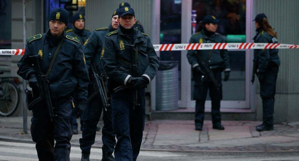 Police officers control the street in front of an internet cafe in Norrebro district in Copenhagen, February 15, 2015