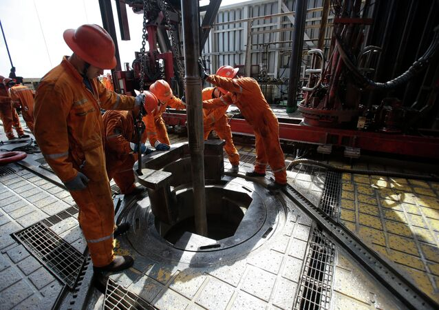 Oil workers lower the drill on the Centenario deep-water drilling platform off the coast of Veracruz, Mexico in the Gulf of Mexico, Friday, Nov. 22, 2013