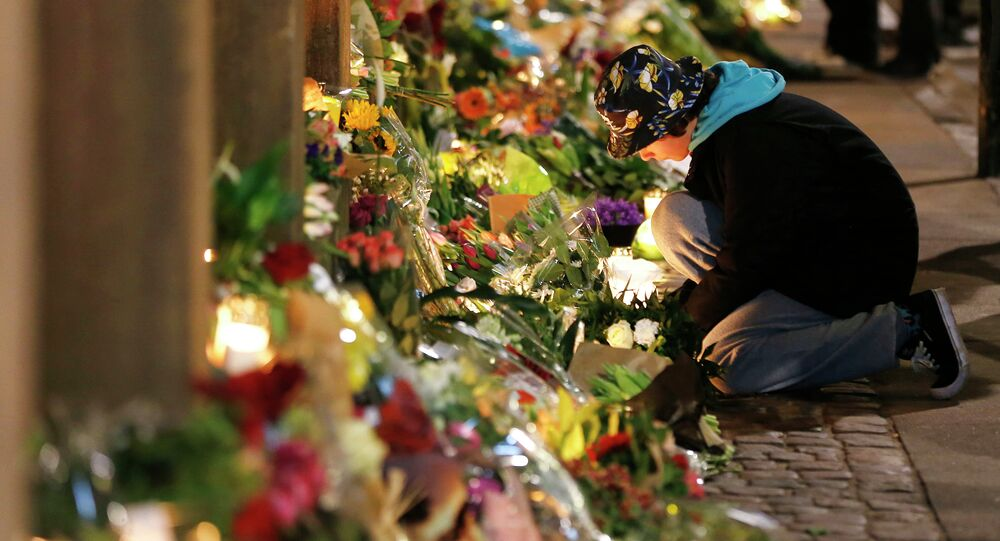 Flowers are placed in front of the synagogue where one person was killed in Copenhagen, Denmark, Sunday, Feb. 15, 2015