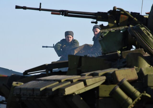 In this Wednesday, Jan. 14, 2015 photo members of the armed forces of the self-proclaimed Luhansk People's Republic sit on top a tank at the check-point north of Luhansk, Eastern Ukraine