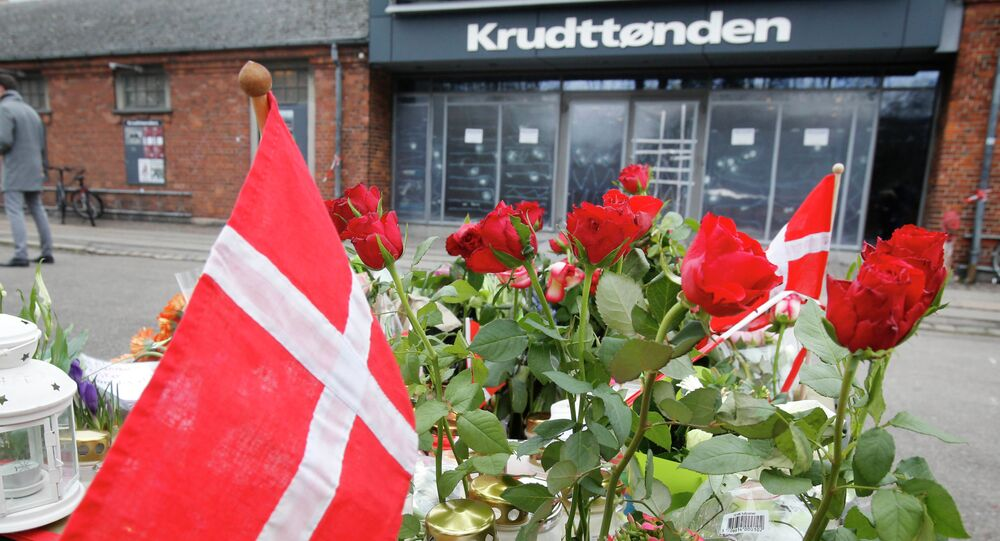 A Danish flag and roses are placed in front of a cultural club in Copenhagen, Denmark, Tuesday, Feb. 17, 2015.