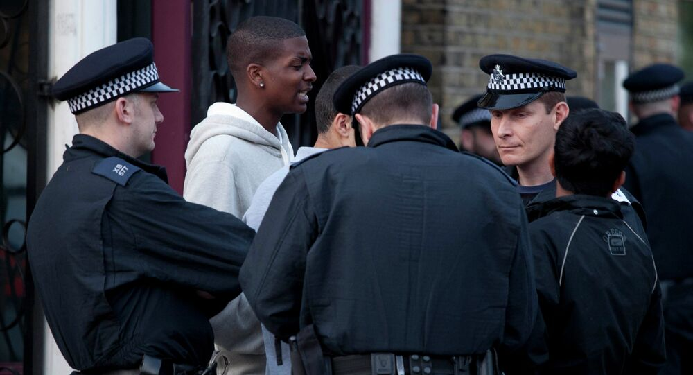 Police officers question men during a routine stop and search operation in Hackney, North London.