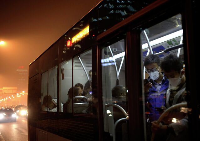 Commuters wearing masks to protect themselves from pollutants check smartphones as they ride on a bus on a hazy day in Beijing, China Monday, Oct. 20, 2014