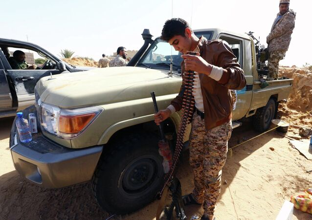 Fighters from the Fajr Libya (Libya Dawn) militia hold a position during clashes with forces loyal to Libya's internationally recognised government as they fight for the control of the area near the Wetia military air base on February 4, 2015 in al-Aqrabiyah, some 170 kilometres west of the capital Tripoli