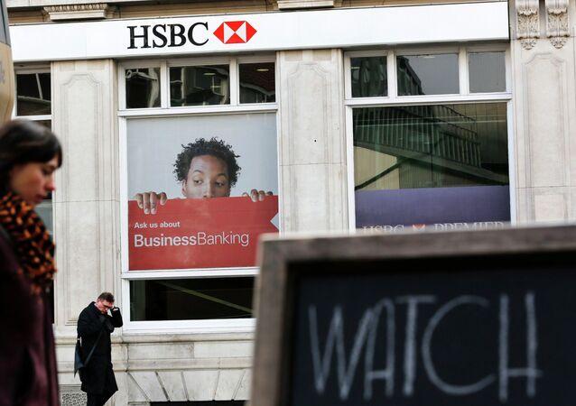 Pedestrians walk past a branch of HSBC bank in London