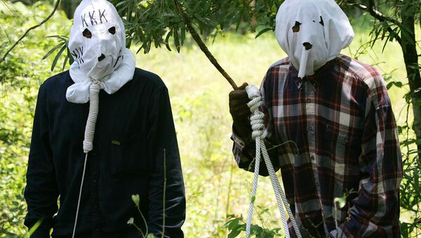 Ben Reed, right, and Keith Christian, left, portraying Klansmen, run through a reenactment of the 1946 lynching at the Moore's Ford Bridge, to raise awareness for the unsolved murders. - Sputnik International