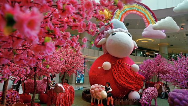 A girl touches a goat decoration as a shopping mall floor is decorated with goat installation to celebrate the upcoming Chinese Lunar New Year in Hong Kong - Sputnik International