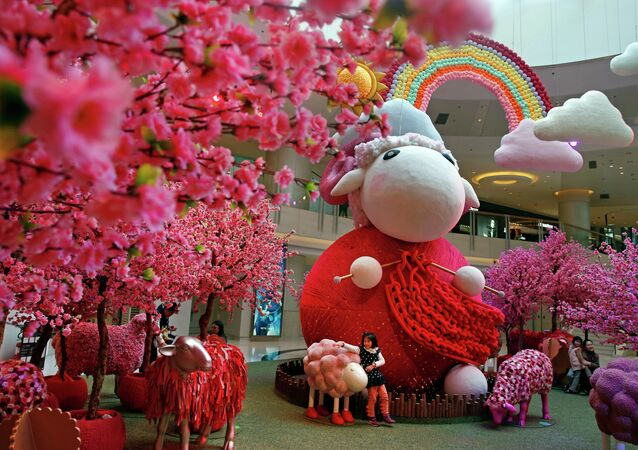 A girl touches a goat decoration as a shopping mall floor is decorated with goat installation to celebrate the upcoming Chinese Lunar New Year in Hong Kong