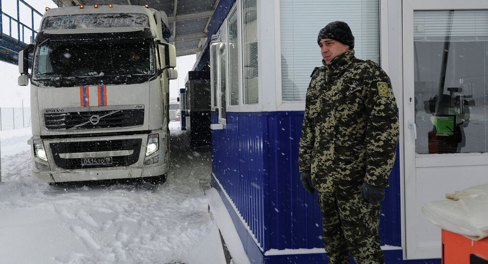 Ukrainian border control officers near a truck of Russia's eighth humanitarian convoy carrying aid for Donbas residents, at the Matveyev Kurgan checkpoint