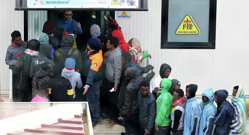 Migrants stand in front of the infirmary at the immigration centre on the southern Italian island of Lampedusa