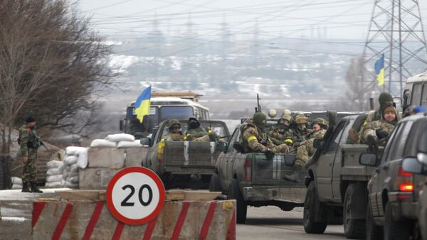 Ukrainian government troops sit in the back of pick-up trucks as they pass a checkpoint near the town of Mariupol, Ukraine - Sputnik International