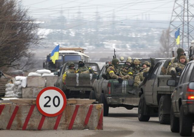 Ukrainian government troops sit in the back of pick-up trucks as they pass a checkpoint near the town of Mariupol, Ukraine