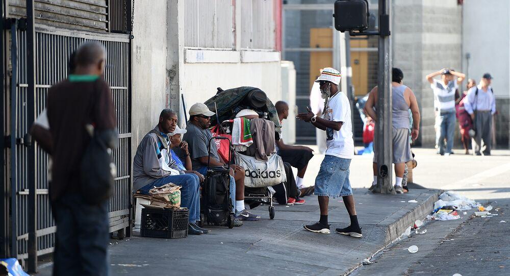 Men sit along a street in Skid Row in Los Angeles, California