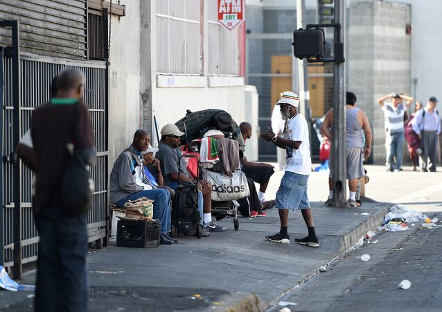 Men sit along a street in Skid Row in Los Angeles, California