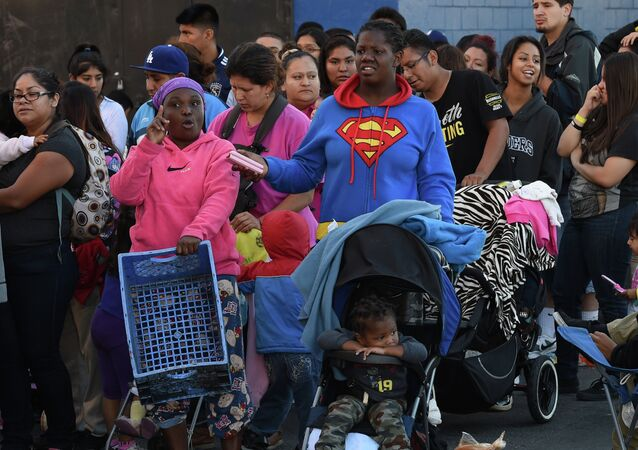 Mothers and their children wait for new shoes and school supplies during a charity event in Los Angeles