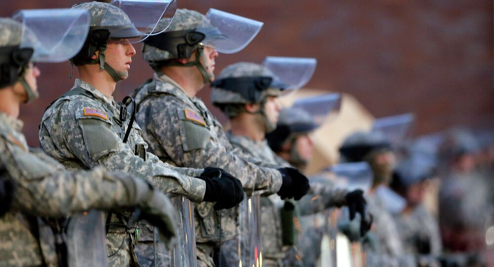 National Guard troops stand in front of the Ferguson, Mo., Police Department a day after a grand jury's decision in the fatal shooting of Michael Brown. Newly released documents reveal that police planning for a grand jury announcement wanted Guard troops and armored Humvees stationed in the Ferguson neighborhood where Brown had been shot.