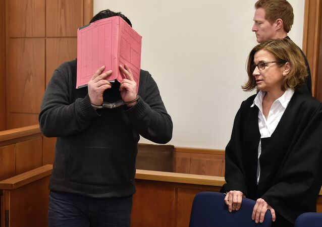 The former nurse identified only as Niels H. hides his face behind a folder while arriving in the courtroom beside his lawyer, Ulrike Baumann, in Oldenburg, Germany.