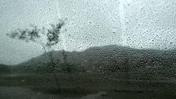 A landscape is seen through a wet window from inside a car in Lima - Sputnik International