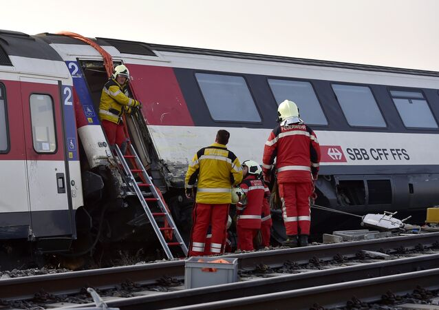 Firefighters inspect the site of a train crash at the train station of Rafz, northern Switzerland, on February 20, 2015