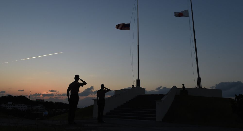 Servicemen of US Marine Corps salute while Japanese (R) and US flags are being taken down at the evening colors ceremony at the Camp Foster near Futenma Base in Ginowan, Okinawa prefecture, on November 14, 2014.