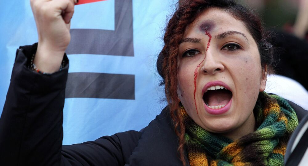 A woman with a bullet hole painted on her forehead takes part in a demonstration against the murder of 20-year-old Ozgecan Aslan.