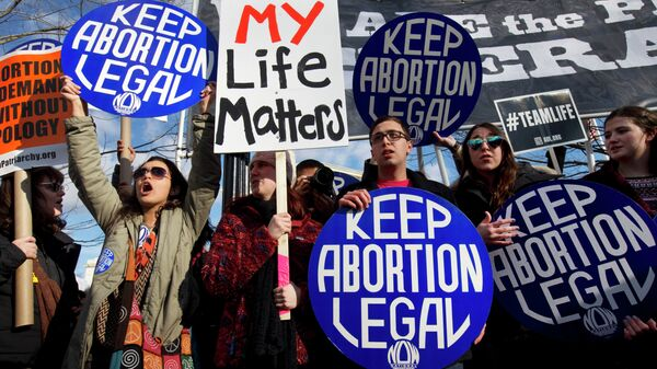 Abortion rights advocates hold signs while anti-abortion demonstrators walk by during the annual March for Life in Washington, DC. - Sputnik International