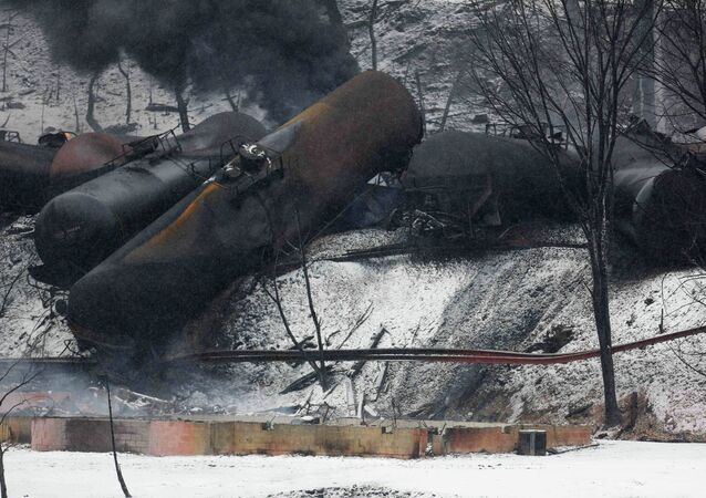 The charred remains of a house and a vehicle are shown below a derailed CSX Corp train in Mount Carbon, West Virginia
