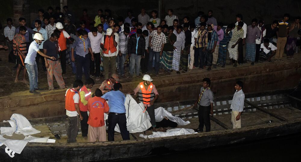 Bangladeshi rescue workers recover the body of a victim after a ferry accident at Paturia some 70kms east of Dhaka on February 22, 2015.