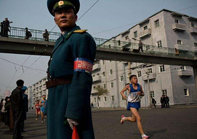 Runners pass under a pedestrian bridge in central Pyongyang during the running of the Mangyongdae Prize International Marathon in Pyongyang, North Korea on Sunday, April 13, 2014