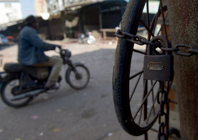 A Pakistani motorcyclist drives past a closed market during a protest strike called by political party Muttahida Qaumi Movement (MQM) following the killing of a senior party worker, in Karachi