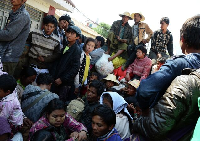 In this Feb. 17, 2015, photo provided by the Eleven Media Group, refugees wait for a Myanmar Red-Cross Team during a clash between government troops and Kokang rebels in Kokang, northeastern Shan State, more than 800 kilometers (500 miles) northeast of Yangon, Myanmar