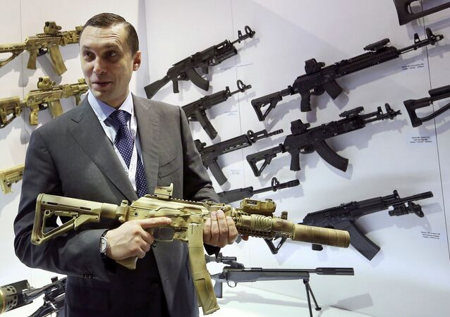 Aleksey Krivoruchko, chief executive of Russian firearms maker Kalashnikov Concern, holds a weapon during the International Defence Exhibition (IDEX) in Abu Dhabi February 22, 2015