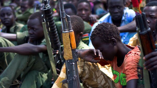 Children soldiers sit on February 10, 2015 with their rifles at a ceremony of the child soldiers disarmament, demobilisation and reintegration in South Sudan. - Sputnik International