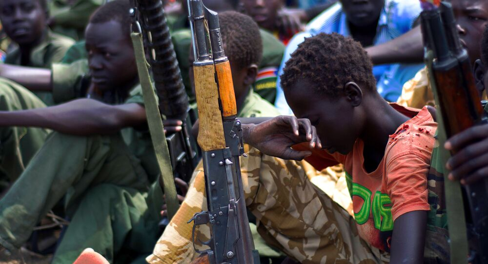 Children soldiers sit on February 10, 2015 with their rifles at a ceremony of the child soldiers disarmament, demobilisation and reintegration in South Sudan.