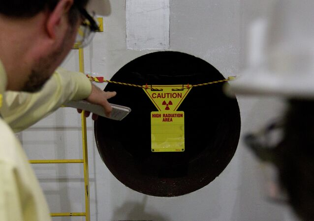 Reporters point to a hole in the wall with a radioactive warning on it near the containment vessel of the Unit 1 reactor during a tour of the Browns Ferry nuclear plant in Athens, Ala., Friday, March 25, 2011