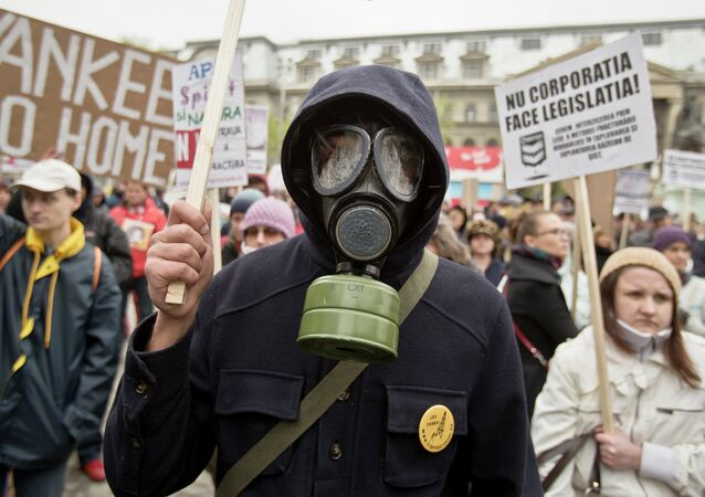 An anti-fracking demonstrator wears a gas mask and holds flowers during a protest in Bucharest, Romania, Sunday, April 6, 2014
