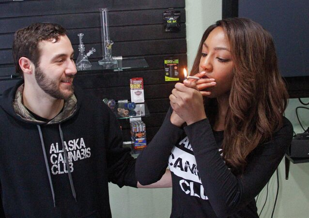 Peter Lomonaco, co-founder of the Alaska Cannabis Club, and CEO Charlo Greene, share a joint at their medical marijuana dispensary in Anchorage, Alaska.