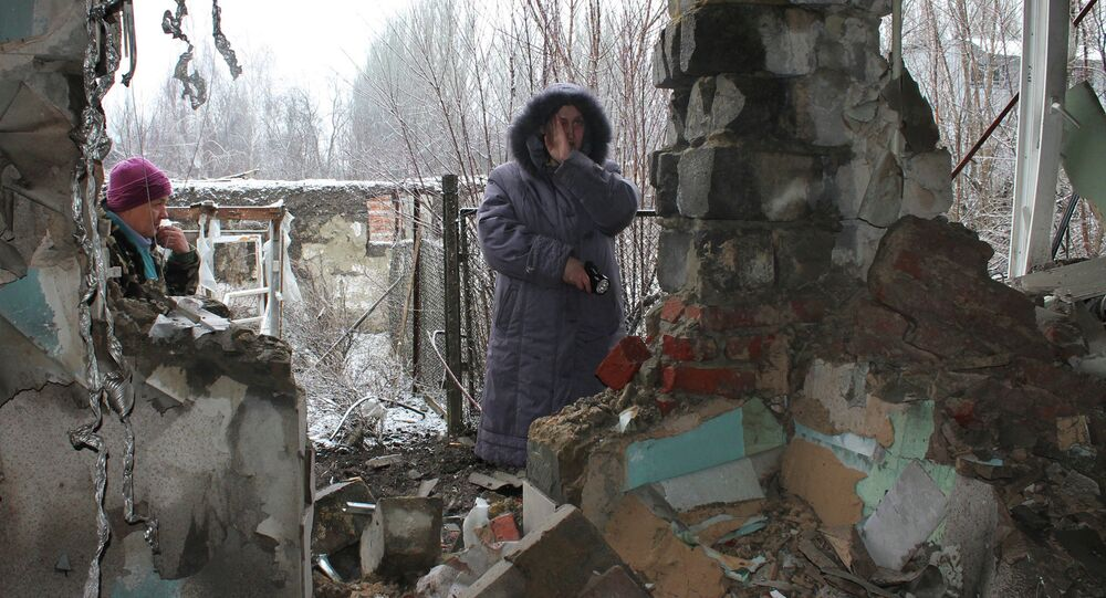 Local residents standing at what has remained of their house after another artillery shelling of Donetsk.