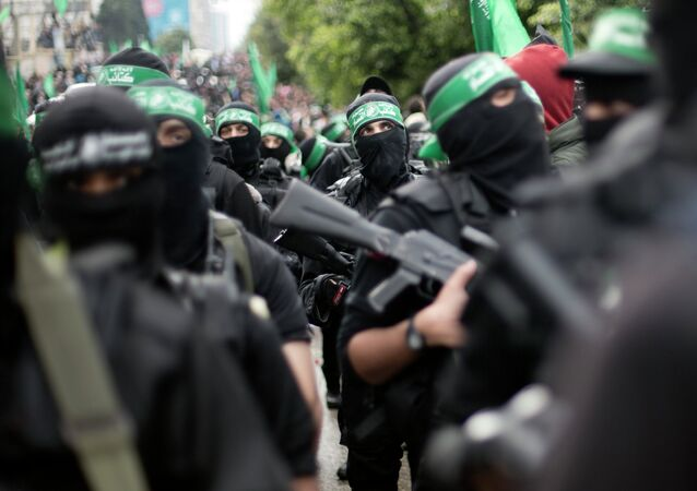Palestinian Hamas masked gunmen display their military skills during a rally to commemorate the 27th anniversary of the Hamas militant group, in Gaza City, Sunday, Dec. 14, 2014