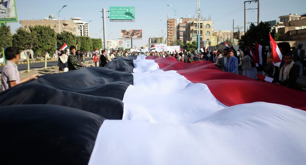 Pro-Houthi protesters carry a Yemeni flag as they march during a demonstration against the U.S. and the U.N. Security Council in Sanaa February 20, 2015