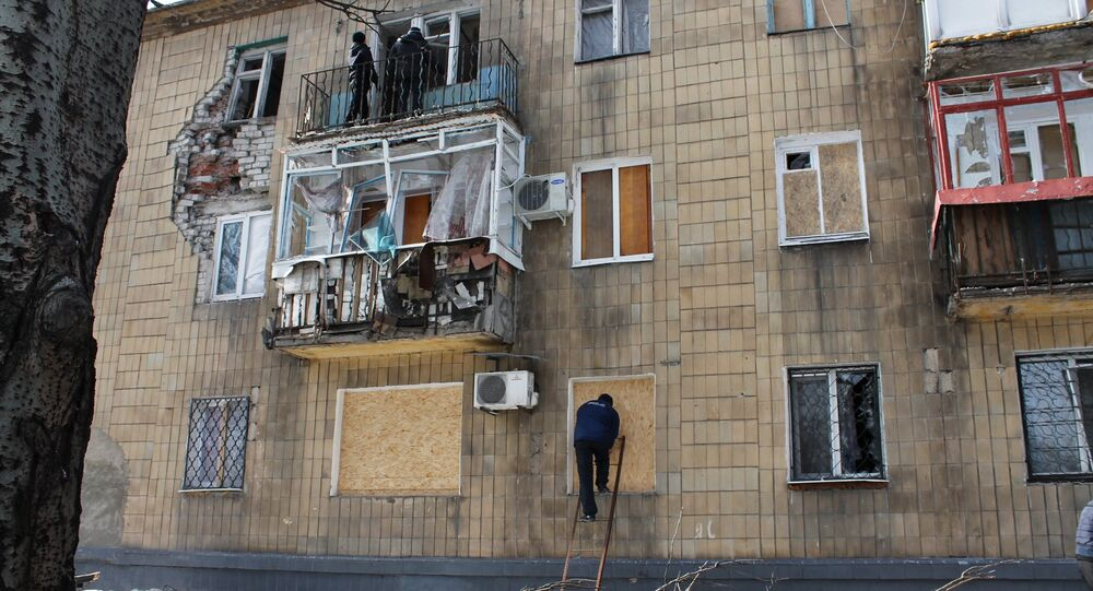 A man covers windows in a building which was damaged by shelling in Donetsk