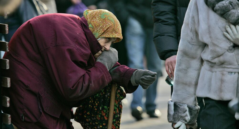 A pensioner begs for money as pedestrians pass by in central Kiev, Ukraine