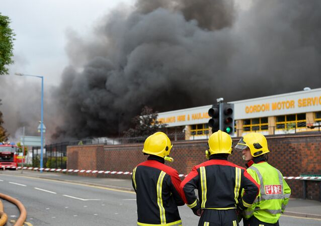Firefighters stand beside a cordon as they tend to a fire at a recycling plant in Smethwick near Birmingham