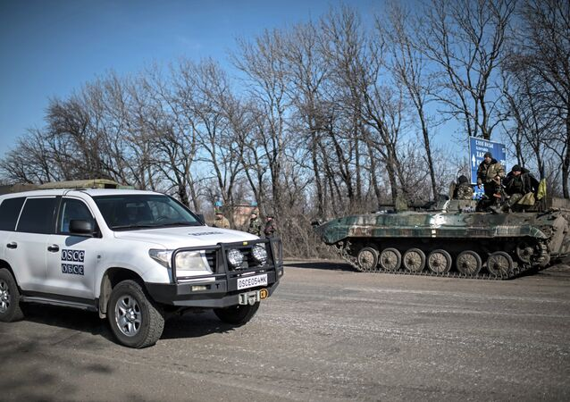 A car of Organization for Security and Co-operation in Europe (OSCE) mission drives past a Ukrainian military vehicle near Artemivsk, eastern Ukraine